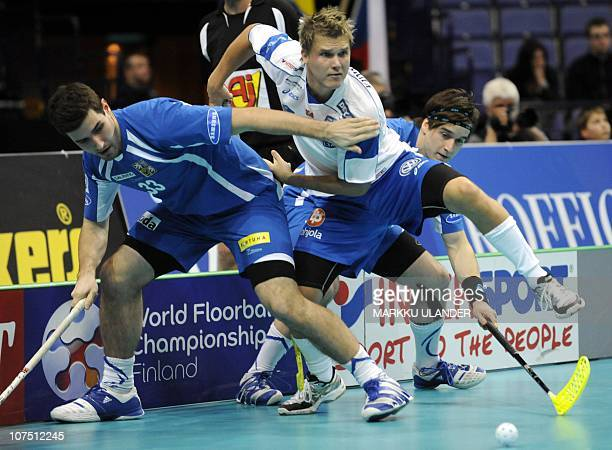 Finland's Jani Kukkola breaks through Czech players Jan Jelinek and Pavel Brus during the World Floorball Championship 2010 semifinal game between...