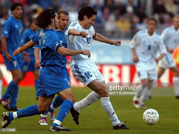 Finland's Jari Litmanen runs ahead of Italy's Gianluca Zambrotta and Alessandro Del Piero during their Euro 2004 qualifier soccer match between...