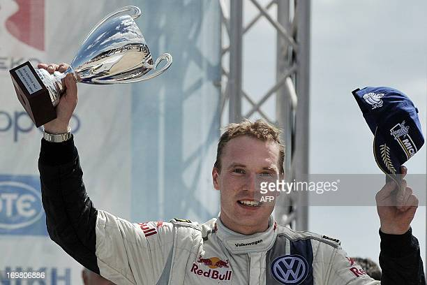 Finland's JariMatti Latvala holds his trophy as he celebrates his victory in the WRC Acropolis rally in Loutraki on June 2 2013 Driving a Volkswagen...