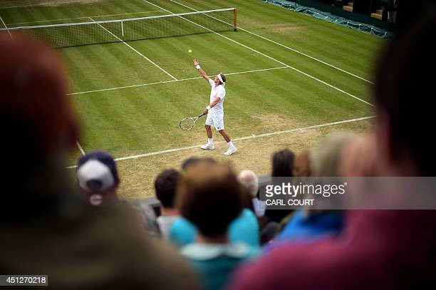 Finland's Jarkko Nieminen serves to US player John Isner during their men's singles second round match on day four of the 2014 Wimbledon...