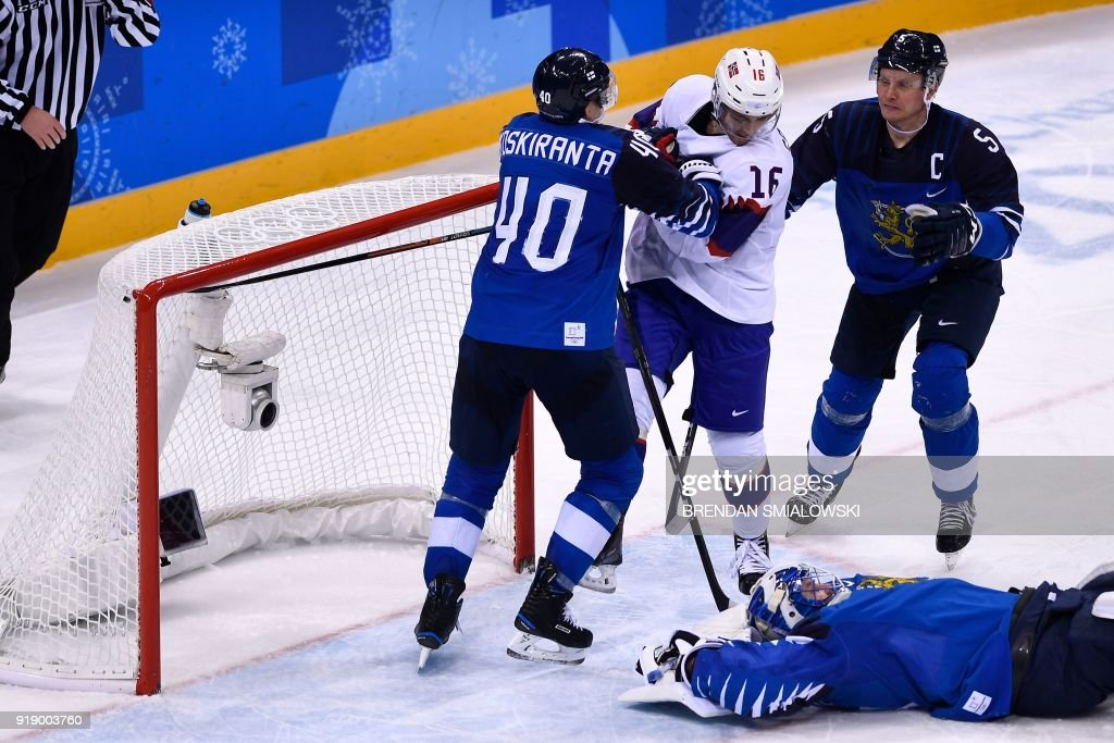 Finland's Jarno Koskiranta (L) and Finland's Lasse Kukkonen (R) confront Norway's Eirik Salsten as Finland's Mikko Koskinen lies on the ice in the men's preliminary round ice hockey match between Finland and Norway during the Pyeongchang 2018 Winter Olympic Games at the Gangneung Hockey Centre in Gangneung on February 16, 2018. / AFP PHOTO / Brendan Smialowski