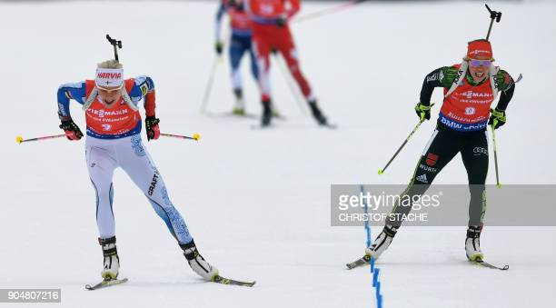 Finland's Kaisa Makarainen and Germany's Laura Dahlmeier compete in front of the finish line during the women 125 kilometer mass start competition of...