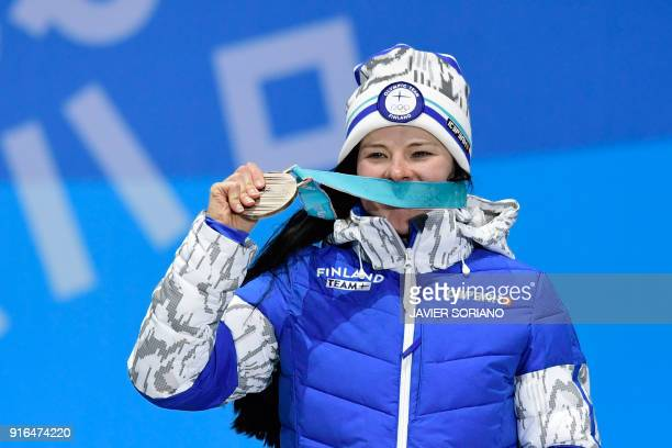 Finland's Krista Parmakoski celebrateS on the podium during the medal ceremony after taking third place in the women's 75km 75km crosscountry...
