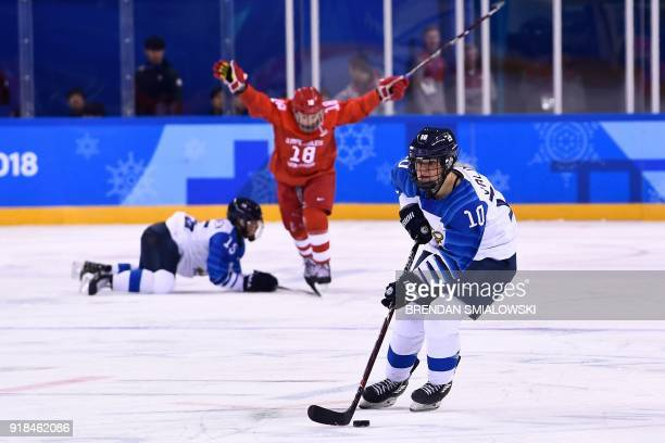 Finland's Linda Valimaki controls the puck in front of teammate Minnamari Tuominen and Russia's Olga Sosina in the women's preliminary round ice...