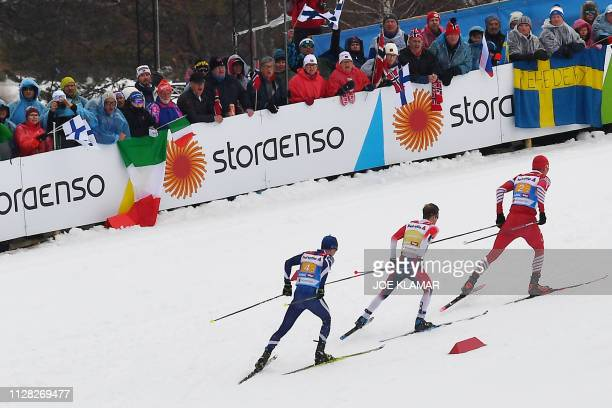 Finland's Matti Heikkinen Norway's Sjur Roethe and Russia's Alexander Bolshunov compete in the Men's cross country skiing relay 4x10km event at the...