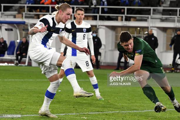 Finland's midfielder Fredrik Jensen scores the opening goal next to Ireland's defender Dara O'Shea during the UEFA Nations League football match...