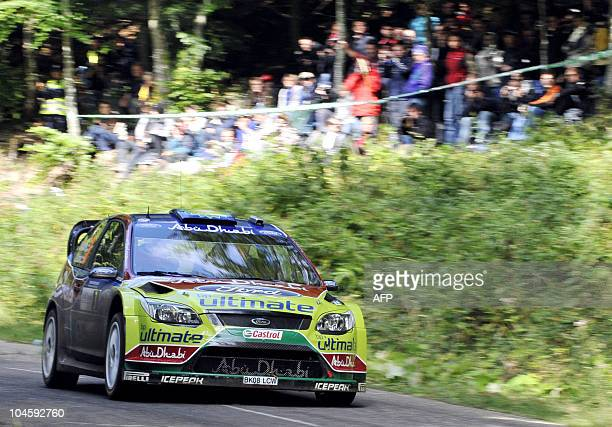 Finland's Mikko Hirvonen and Finland's codriver Jarmo Lehtinen steer their Ford Focus RS WRC in a curve near Osenbach eastern France on October 01...