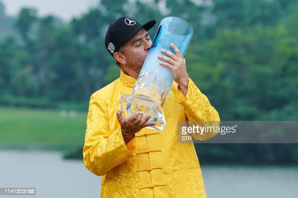 Finland's Mikko Korhonen kisses the trophy after winning the China Open golf tournament in Shenzhen in China's southern Guangdong province on May 5...
