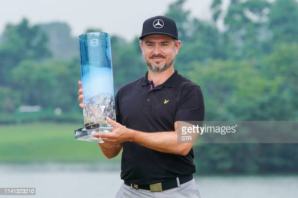 Finland's Mikko Korhonen poses with the trophy after winning the China Open golf tournament in Shenzhen in China's southern Guangdong province on May...