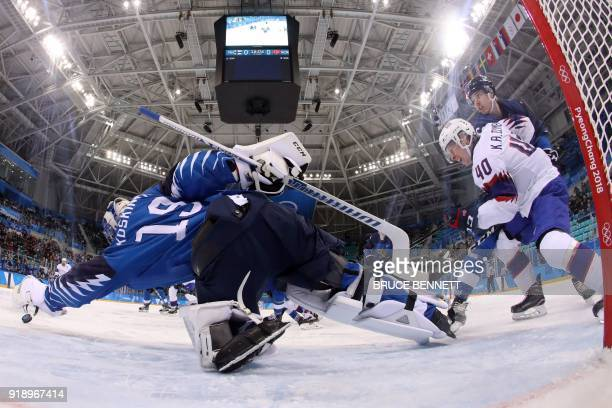 Finland's Mikko Koskinen dives for a puck shot by Norway's Ken Andre Olimb in the men's preliminary round ice hockey match between Finland and Norway...