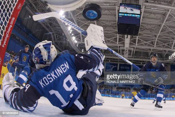 Finland's Mikko Koskinen lets in a goal by Sweden's Patrik Zackrisson in the men's preliminary round ice hockey match between Sweden and Finland...