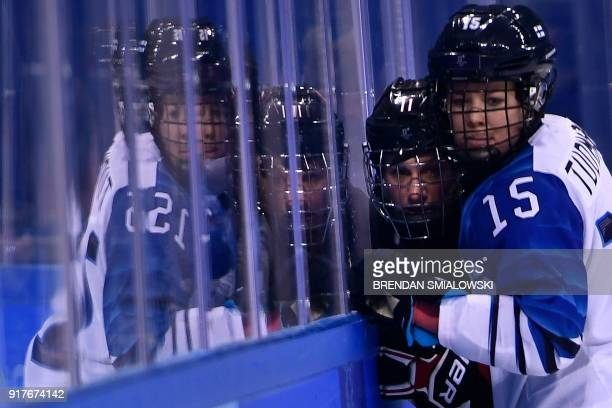 Finland's Minnamari Tuominen pins Canada's Jillian Saulnier against the glass during the final period of the women's preliminary round ice hockey...
