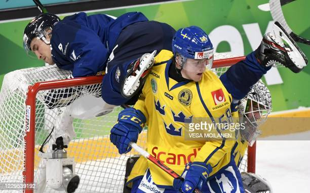 Finland's Otto Karvinen vies with Sweden's Jesper Sellgren during the Ice Hockey Karjala Tournament match between Finland and Sweden as part of the...