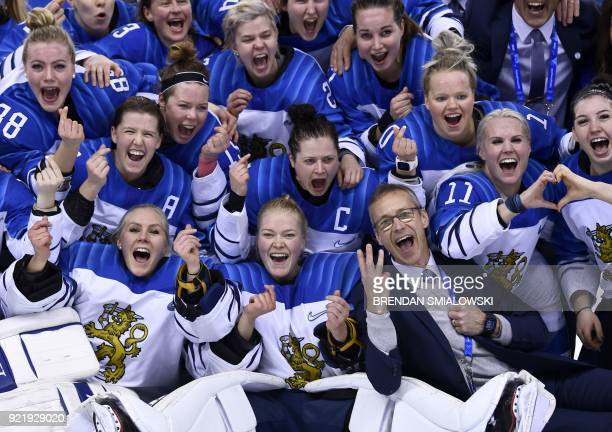 TOPSHOT Finland's players and coach Lauri Marjamaki celebrate winning the women's bronze medal ice hockey match between Finland and the Olympic...