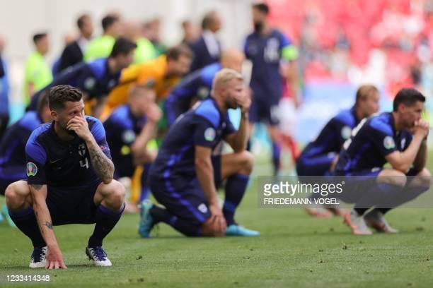 Finland's players react as paramedics attend to Denmark's midfielder Christian Eriksen during the UEFA EURO 2020 Group B football match between...