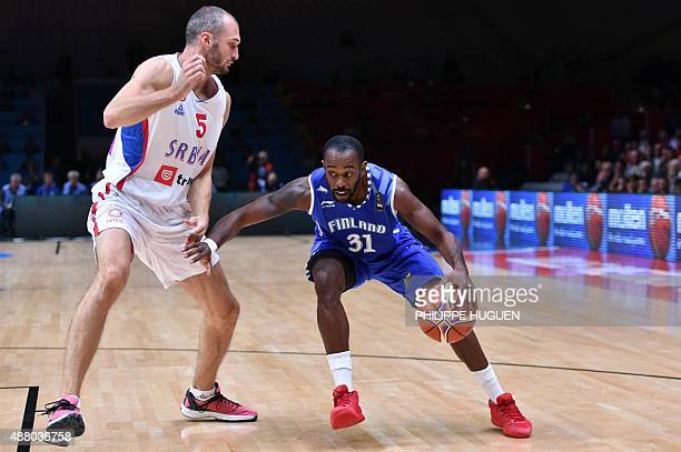 Finland's point guard Jamar Wilson dribbles around Serbia's small forward Marko Simonovic during the round of 16 basketball match between Serbia and...