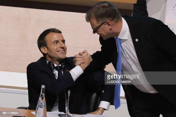Finland's Prime Minister Juha Sipila shakes hands with French President Emmanuel Macron during the plenary session of the One Planet Summit on...