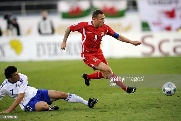 Finland's Roman Eremenko fails to tackle Craig Bellamy of Wales during the World Cup qualifying match Finland vs Wales in Helsinki Olympic Stadium on...