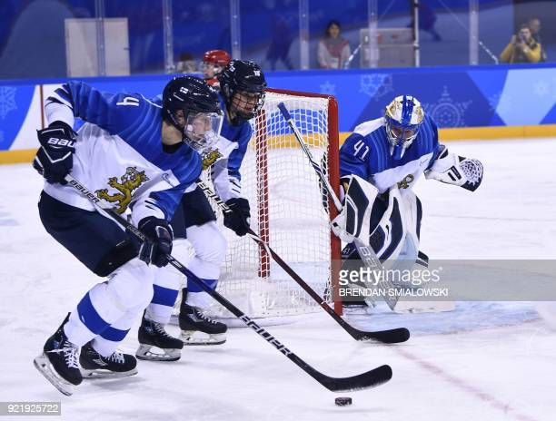 Finland's Rosa Lindstedt tries to get the puck around the net in the women's bronze medal ice hockey match between Finland and the Olympic Athletes...