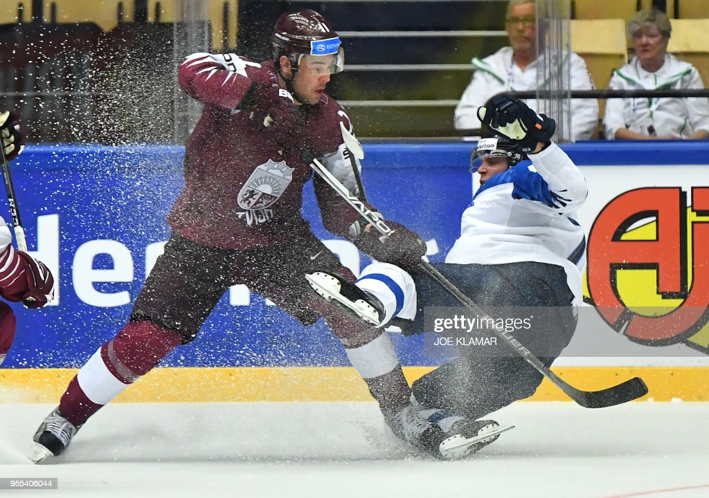 Finland's Saku Maenalanen (R) fights for the puck with Latvia's Kristaps Sotnieks during the group B match Latvia vs Finland of the 2018 IIHF Ice Hockey World Championship at the Jyske Bank Boxen in Herning, Denmark, on May 6, 2018.