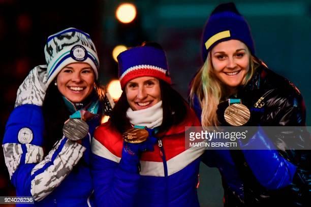 TOPSHOT Finland's silver medallist Krista Parmakoski Norway's gold medallist Marit Bjoergen and Sweden's bronze medallist Stina Nilsson pose on the...