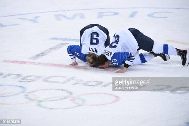 TOPSHOT Finland's Venla Hovi and Michelle Karvinen kiss the ice after winning the women's bronze medal ice hockey match between Finland and the...