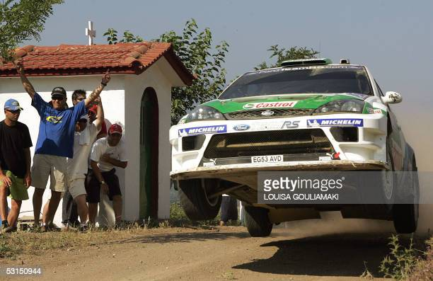 Finland'sToni Gardeimester and co driver Jakke Honkanen jump with their Ford Focus WRC while driving past a chapel at the Grammeni special stage...