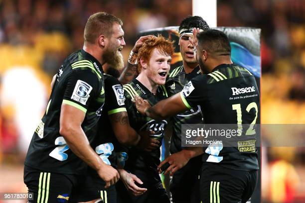 Finlay Christie of the Hurricanes celebrates with Matt Proctor Brad Shields Vince Aso and Reed Prinsep after scoring a try on debut during the round...