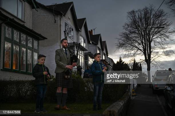 Finlay MacDonald and his sons Elliott ten and Fionn eight play Scotland the Brave on the bagpipes outside their home in Clarkston on April 02 2020 in...