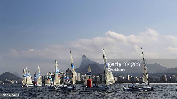 Finn class boats in action with Christ the Redeemer in the background on Day 4 of the Rio 2016 Olympic Games at the Marina da Gloria on August 9 2016...