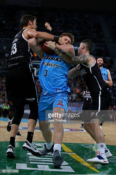 Finn Delany of the Breakers is fouled be David Anderson and Nate Tomlinson of Melbourne United during the round five NBL match between Melbourne...