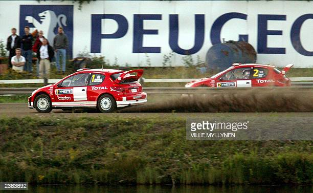Finn Marcus Gronholm edges out teammate Richard Burns to place second in the first leg SuerSpecial Stage of Rally Finland 07 August 2003 in Jyvaskyla...