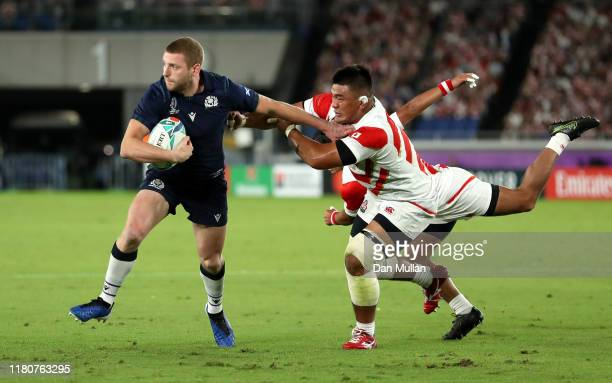 Finn Russell of Scotland hands off Jiwon Koo of Japan as he scores their first try during the Rugby World Cup 2019 Group A game between Japan and...