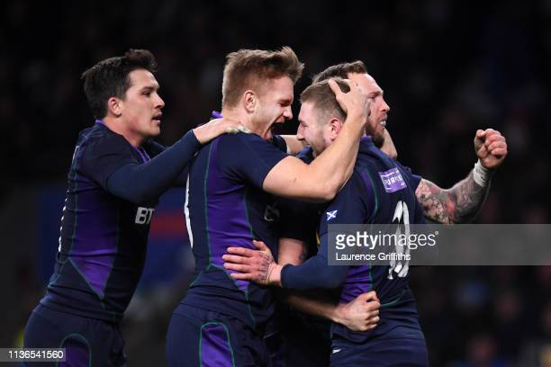 Finn Russell of Scotland is congratulated by Chris Harris and Byron McGuigan after scoring the fifth try during the Guinness Six Nations match...