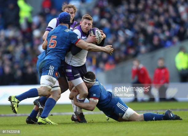 Finn Russell of Scotland is tackled by Guilhem Guirado and Wenceslas Lauret during the Six Nations match between Scotland and France at Murrayfield...