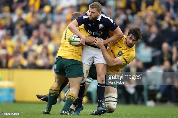 Finn Russell of Scotland is tackled by Tom Robertson and Sam Carter of the Wallabies during the International Test match between the Australian...