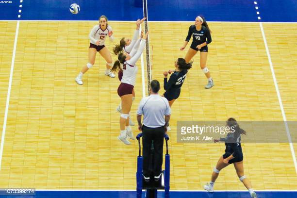 Finn Wilkins of Emory University centerright spikes the ball against Calvin College during the Division III Women's Volleyball Championship held at...
