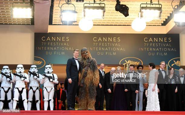 Finnish actor Joonas Suotamo who plays Chewbacca poses with Chewbacca as they arrive on May 15 2018 with US actor Woody Harrelson US director Ron...