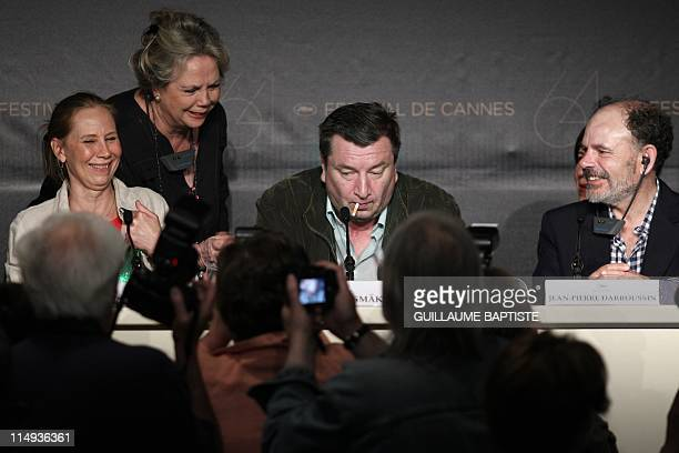 Finnish director Aki Kaurismaki puts a lit cigarette inside his mouth next to French actor JeanPierre Darroussin and Finnish actress Kati Outinen as...
