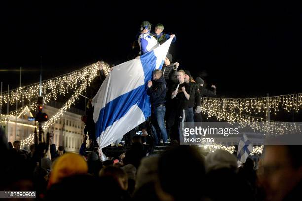 Finnish fans celebrate victory at a fountain in central Helsinki after the UEFA Euro 2020 Group J qualification football match between Finland and...