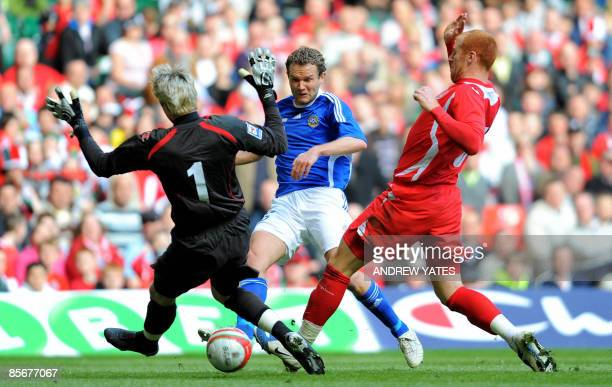 Finnish football striker Jonatan Johansson scores the opening goal past Wales' Wayne Hennessey and Wales' James Collins during the FIFA World Cup...