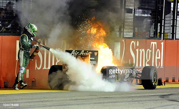 OUT Finnish Formula One driver Heikki Kovalainen tries to extinguish his car after it caught fire during the Formula One's Singapore Grand Prix at...
