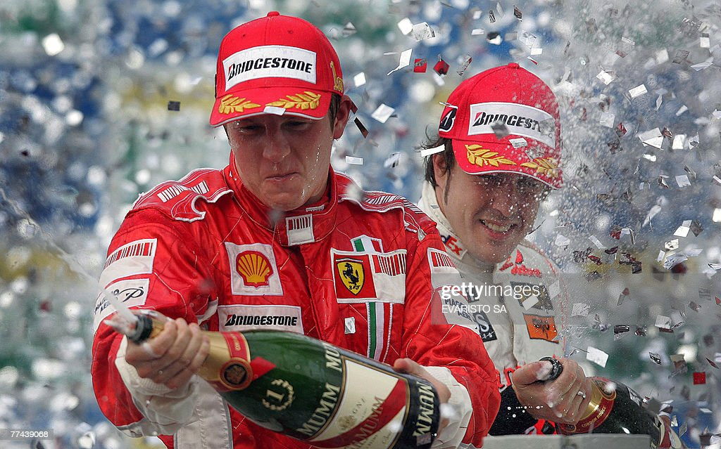 Finnish Formula One drivers Kimi Raikkonen (L) and Spanish Fernando Alonso spray champagne during the podium ceremony of Brazil's Formula One GP, 21 October 2007 at the Interlagos racetrack in Sao Paulo, Brazil. Raikkonen won the race and the World Championship's title, Brazilian Felipe Massa arrived second and Alonso in third place. AFP PHOTO