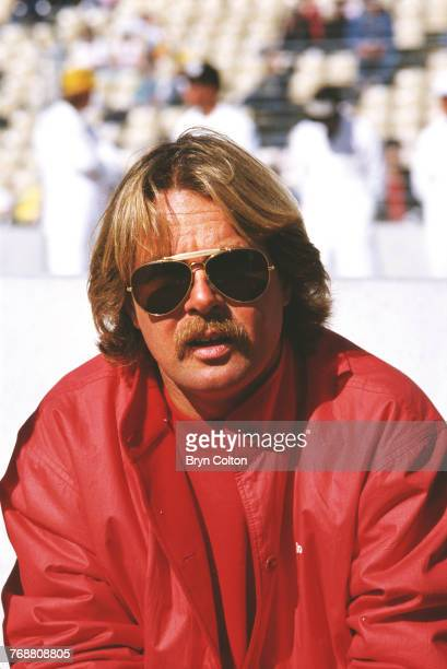 Finnish Formula One racing driver Keke Rosberg, of the McLaren-TAG team, sits on the wall of the pit lane ahead of the 1986 Australian Grand Prix at...