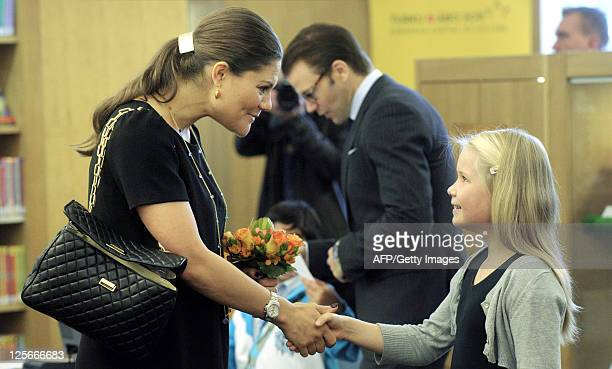 Finnish girl Saana Järvi presents flowers to Crown Princess Victoria in a library in Turku on September 20 2011 The Swedish princess and her husband...
