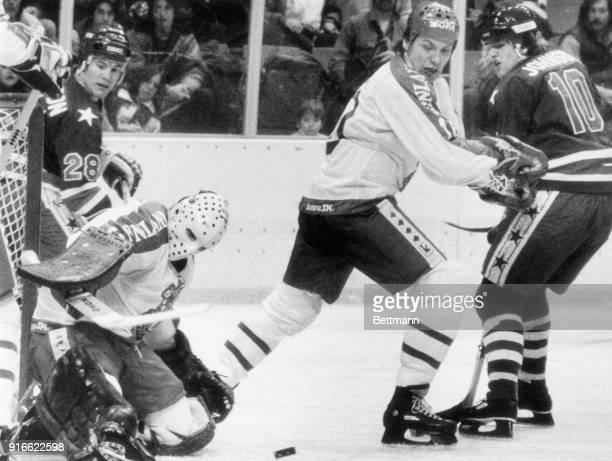 Finnish goalie, Jorma Valtonen, blocks a shot on goal by America's Mark Johnson as John Harrington comes up to try for the rebound.