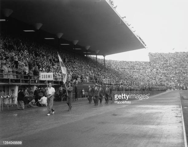 Finnish hurdler Vaino Suvivuo is the flag bearer leading the Finnish Olympic team at the opening ceremony of the 1952 Summer Olympics at the Helsinki...