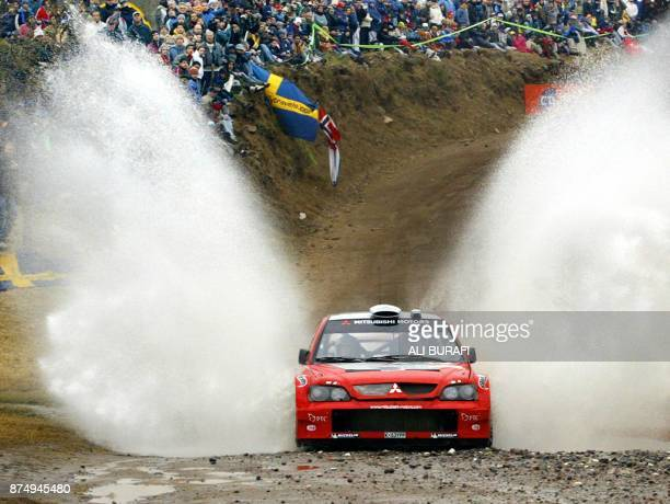 Finnish Kristian SohlbergKaj Lindstroem's Mitsubishi Lancer crosses a puddle during the second stage of the Rally of Argentina 17 July 2004 in...