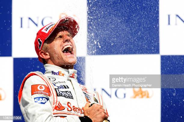 Finnish McLaren Formula One driver Heikki Kovalainen celebrates by spraying champagne on the winners podium after winning the 2008 Hungarian Grand...