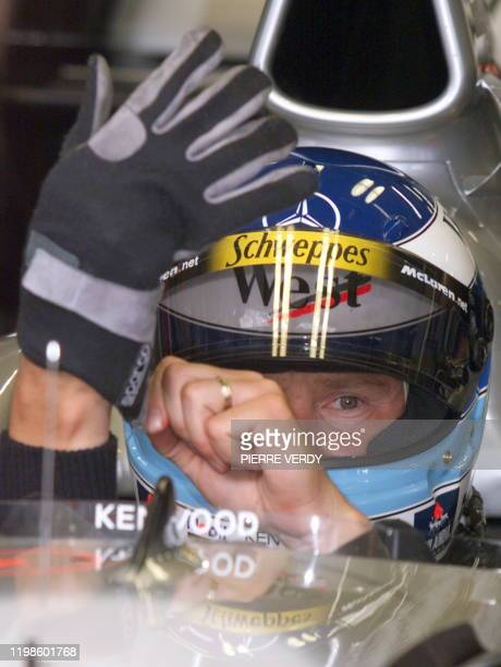 Finnish McLarenMercedes driver Mika Hakkinen puts his gloves on during the qualifying session in Spielberg 24 July 1999 on the eve of the Austrian...